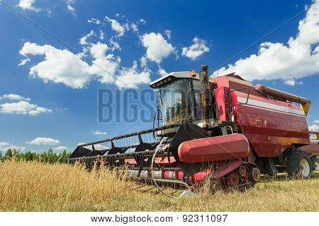 Combine Harvester At The Edge Of Grain Field During Harvest Time