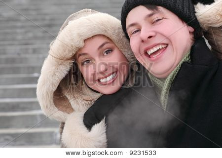 Young Girl In Coat With Hood Embracing Man From Back And Laughing, Half Body, Winter Day