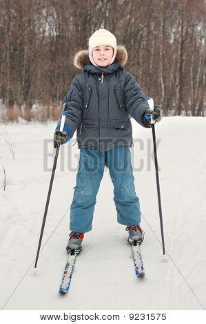 Little Boy In Warm Sport Dress Skiing At Forest, Full Body, Looking At Camera