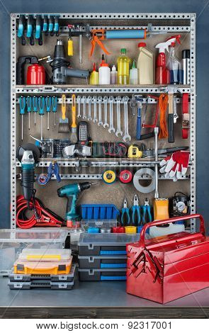 Garage tool rack with various tools and repair supplies on board and shelves.