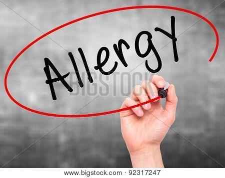 Man Hand writing Allergy with marker on transparent wipe board.
