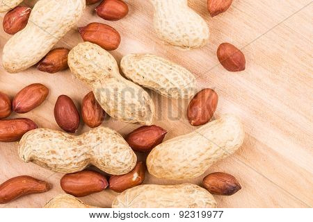 Close up of peanuts on wood.