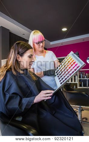 Woman looking with hairdresser a hair dye palette