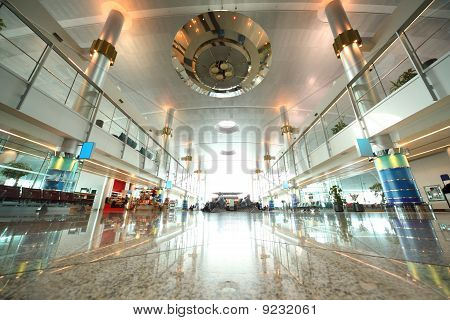 Large Hall With Chairs, Granite Floor And Columns In Dubai International Airport