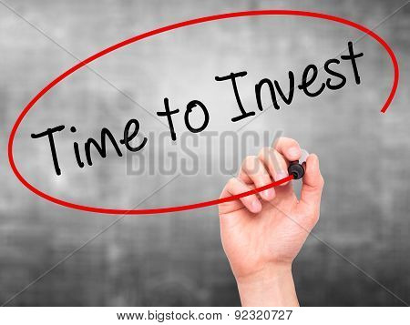Man Hand writing Time to Invest with marker on transparent wipe board.