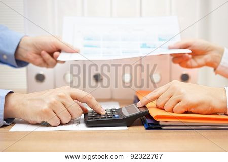 Business People Working Together On Project. They Exchange Report Document And Calculating Prices
