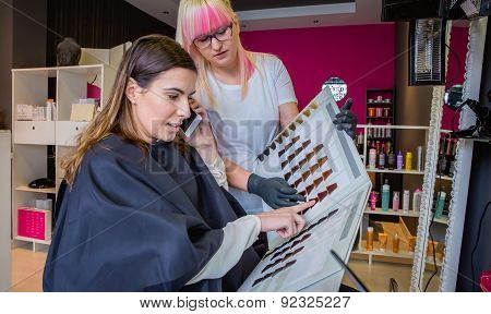 Woman with smartphone looking a hair dye palette