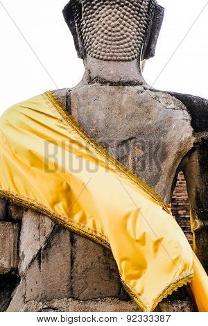 back of ancient Buddha sculpture with yellow shiny robe