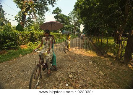 Women Holding Umbrellas Bicycling On Dirt Road In Nepal