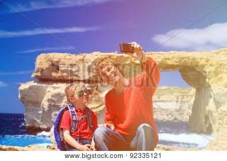father and son making selfie against Azure Window on Gozo island