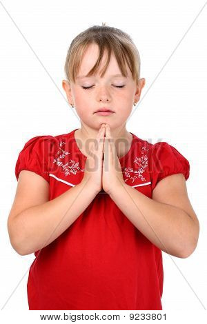 Small girl with clasped hands and eyes closed praying isolated on white