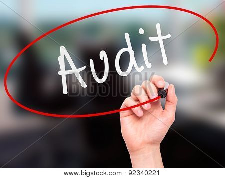 Man Hand writing Audit with marker on transparent wipe board.