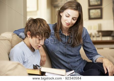 Mother Helping Son With Homework Sitting On Sofa At Home