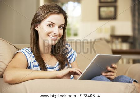 Woman Sitting On Sofa At Home Using Tablet Computer