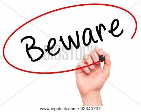 Man Hand writing Beware with marker on transparent wipe board.
