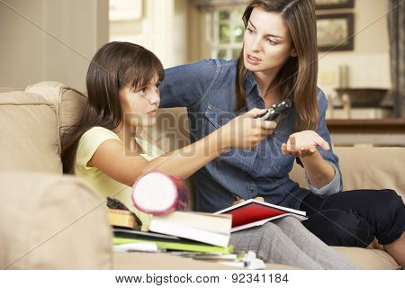 Mother Becoming Frustrated As Daughter Watches TV Whilst Doing Homework Sitting On Sofa At Home