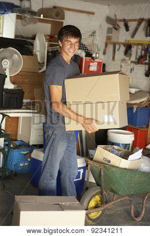 Teenage Boy Clearing Garage For Yard Sale