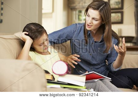 Mother Becoming Frustrated With Daughter Whilst Doing Homework Sitting On Sofa At Home