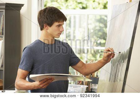 Teenage Boy Working On Painting In Studio