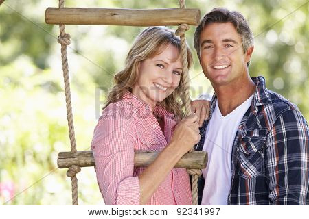 Middle Aged Couple In Garden By Treehouse
