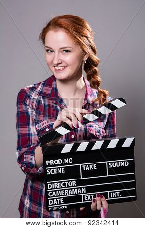 Beautiful Smiling Red-haired Woman Holding A Movie Clapper.