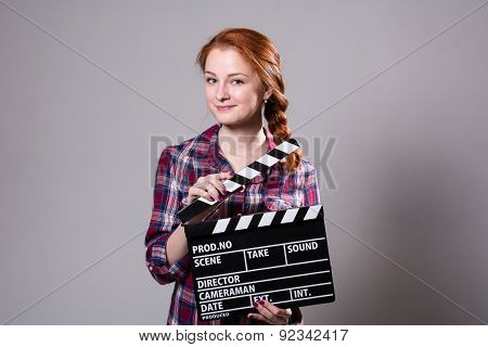 Beautiful Red-haired Woman Holding A Movie Clapper, Isolated Over Gray Background