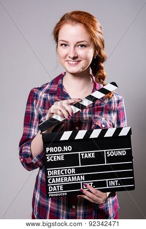 Beautiful Smiling Red-haired Woman Holding A Movie Clapper