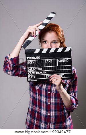 Beautiful Red-haired Woman Holding A Movie Clapper.