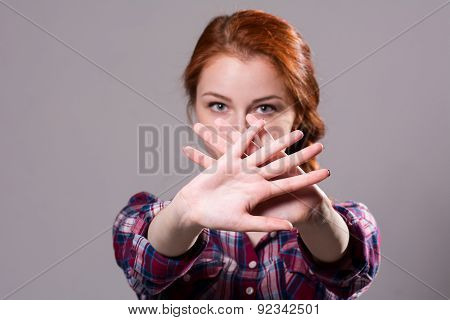 Out Of Focus Woman With Her Hands Signaling To Stop Isolated On A Grey Background