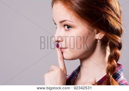 Psst - A Beautiful Girl With Pigtails Making A Shushing Gesture Raising Her Finger To Her Lips