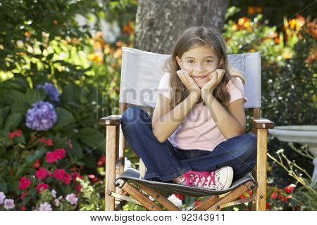 Young Girl Sitting Outdoors In Garden Chair
