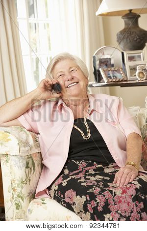 Retired Senior Woman Sitting On Sofa At Home On Phone