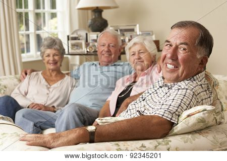 Group Of Retired Friends Sitting On Sofa At Home Together