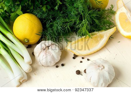 Slices Of Lemon, Garlic Cloves And Parsley On The White Background