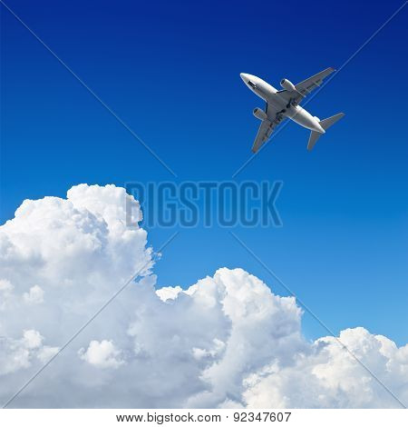 Airplane Flying In The Blue Sky With Clouds