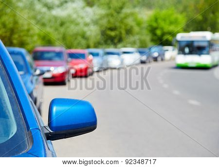 Cars Parked On The Roadside, Bus In The Background
