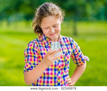 Sweet Smiling Teenage Girl In Casual Clothes With Smartphone In Her Hand, Looking At Screen