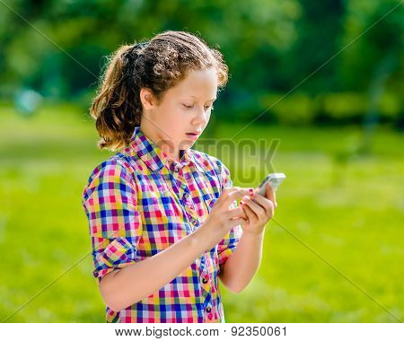 Surprised Teenage Girl In Casual Clothes With Smartphone In Her Hand, Looking At Screen