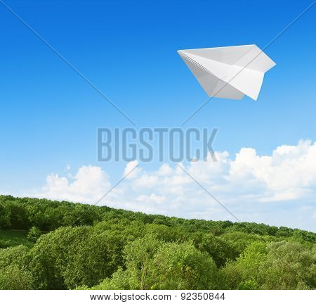 Paper Airplane Flying In The Sky Over The Forest