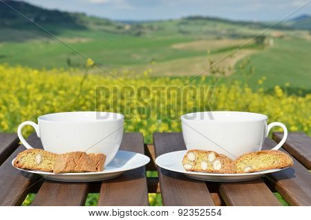 Two coffee cups and cantuccini on the wooden table against Tuscan landscape, Italy