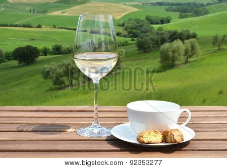 Coffee cup, cantuccini and white wine on the wooden table against olive grove. Tuscany, Italy
