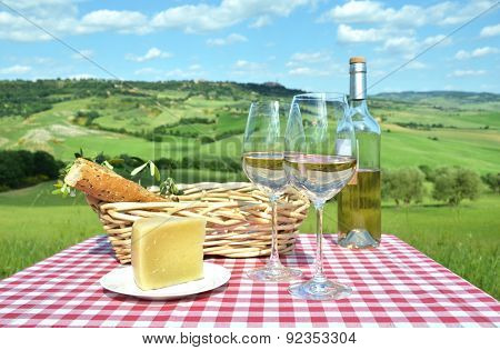 White wine, cheese and bread on the chequered cloth against Tuscan landscape. Italy