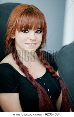 Rebellious teenager girl with red hair sit on the sofa