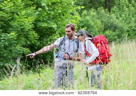 Backpackers on hiking journey looking at vegetation