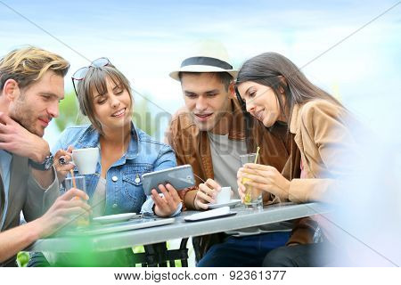 Young people at coffee shop table looking at pictures on smartphone