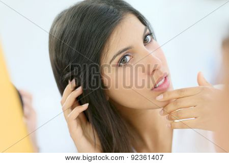 Portrait of beautiful young woman looking at her skin