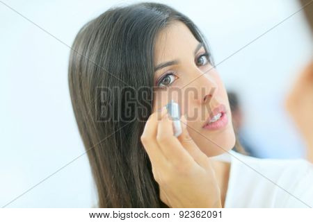 Beautiful brunette woman applying concealer