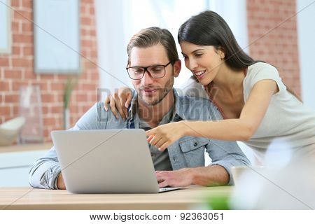 Couple at home websurfing on laptop computer
