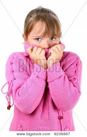 Small girl in pink sweater feeling cold embracing herself looking at camera isolated on white