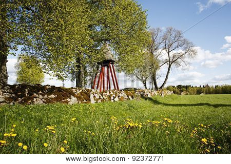 old bell tower and stone hedge, set in a rural landscape, culture from Sweden
